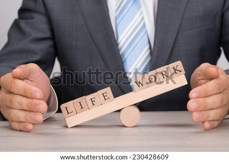 Midsection of businessman covering imbalance between Life and Work on seesaw at table - stock photo