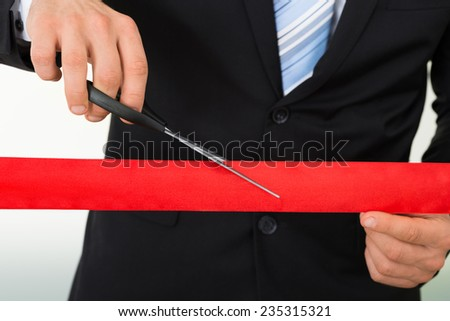 Midsection of businessman cutting red ribbon with scissors over white background - stock photo