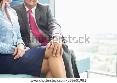 Midsection of businessman flirting with female colleague in office - stock photo