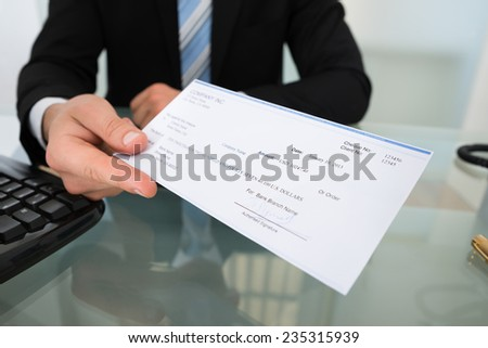 Midsection of businessman giving cheque at desk in office - stock photo