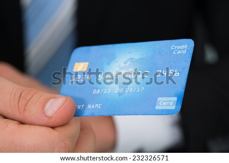 Midsection of businessman giving credit card at desk in office - stock photo