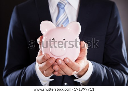 Midsection of businessman holding piggybank against black background - stock photo