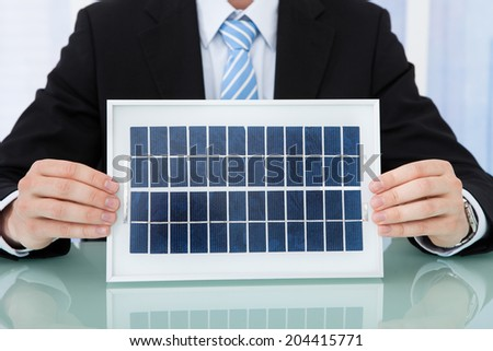 Midsection of businessman holding solar panel at office desk - stock photo