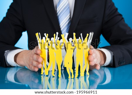 Midsection of businessman protecting successful paper people at desk against blue background - stock photo