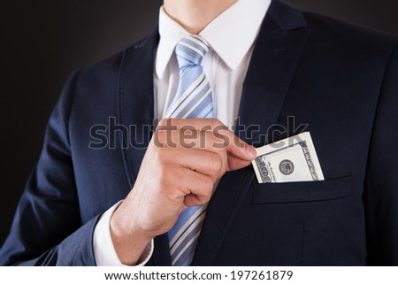 Midsection of businessman putting money in pocket against black background - stock photo