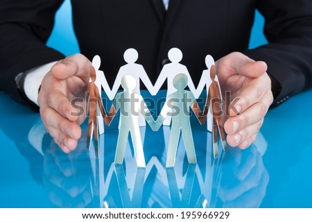 Midsection of businessman's hands protecting team of paper people on desk against blue background - stock photo