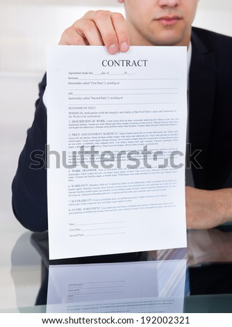 Midsection of businessman showing contract paper at desk in office - stock photo