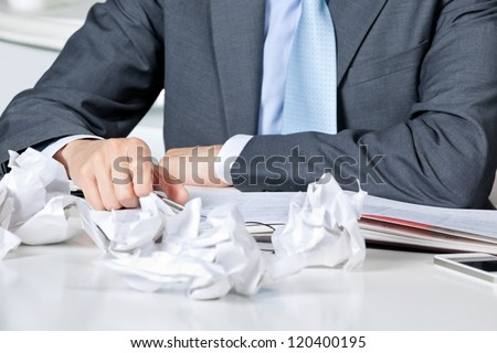 Midsection of businessman sitting at desk with crumpled papers - stock photo