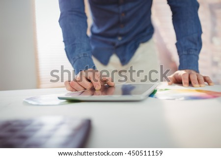 Midsection of businessman using digital tablet on desk at office - stock photo