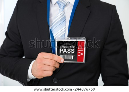 Midsection of businessman with backstage pass in office - stock photo