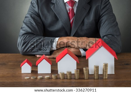 Midsection of businessman with different size houses and stacks of coins on table - stock photo
