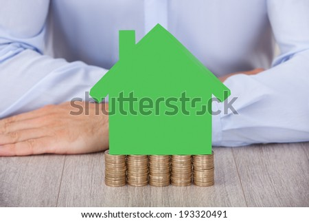 Midsection of businessman with green house model on stacked coins at desk - stock photo