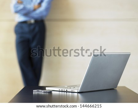 Midsection of businessman with laptop and cell phone on desk in foreground - stock photo