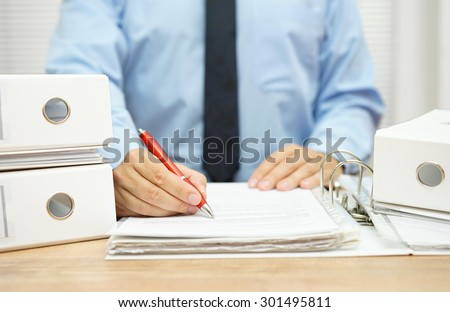 Midsection of businessman working  with financial documents at desk - stock photo