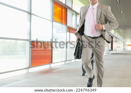 Midsection of businessmen rushing on railroad platform - stock photo