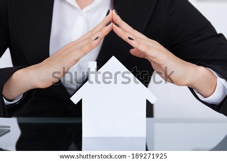 Midsection of businesswoman covering house model at desk in office - stock photo