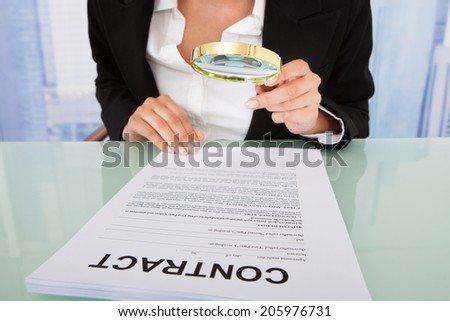 Midsection of businesswoman scrutinizing contract with magnifying glass at office desk - stock photo
