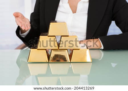 Midsection of businesswoman showing stacked gold blocks on desk in office - stock photo