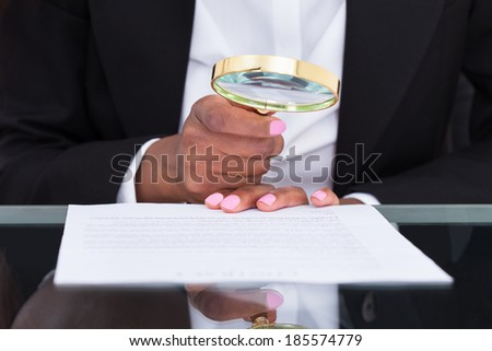 Midsection of businesswoman using magnifying glass to read document at desk in office - stock photo
