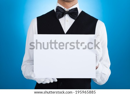 Midsection of butler holding blank billboard over blue background - stock photo