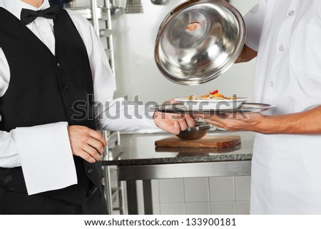 Midsection of chef giving pasta dish to waiter in restaurant kitchen