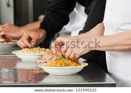 Midsection of chefs garnishing pasta dishes in restaurant kitchen
