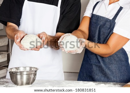 Midsection of chefs presenting dough in commercial kitchen