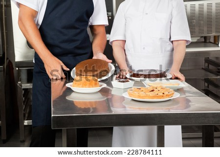 Midsection of chefs with sweet dishes at commercial kitchen counter - stock photo