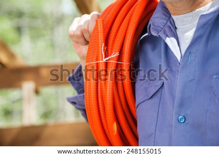 Midsection of construction worker with rolled pipe at site - stock photo
