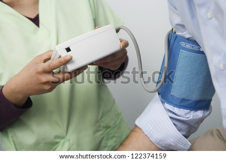 Midsection of doctor checking blood pressure of patient - stock photo