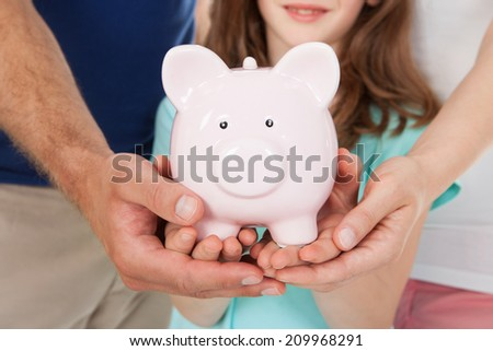 Midsection of family holding piggy bank together - stock photo