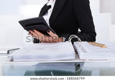 Midsection of female accountant calculating tax at desk in office - stock photo