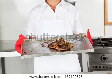 Midsection of female chef holding tray of meat in commercial kitchen - stock photo