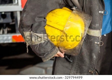 Midsection of female firefighter holding yellow helmet at fire station