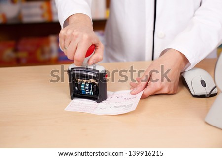 Midsection of female pharmacist stamping bill at pharmacy desk - stock photo