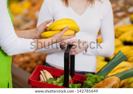 Midsection of female worker assisting customer in purchasing bananas at grocery store - stock photo