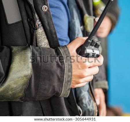Midsection of firefighter holding walkie talkie at fire station - stock photo