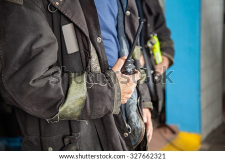 Midsection of fireman holding walkie talkie at fire station - stock photo