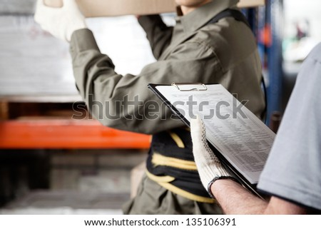 Midsection of foreman loading cardboard box with supervisor holding clipboard at warehouse - stock photo