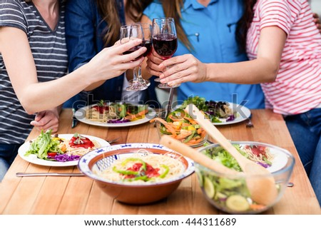 Midsection of friends toasting red wine glasses at table