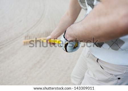 Midsection of golfer racking sand at golf course - stock photo