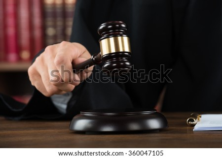 Midsection of judge hitting mallet at desk in courtroom - stock photo