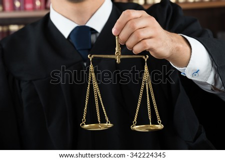 Midsection of judge holding justice scale in courtroom - stock photo