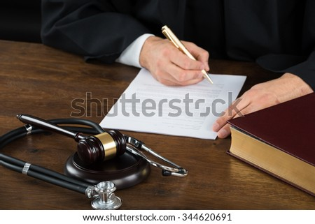 Midsection of judge writing on legal documents with mallet and stethoscope at desk in courtroom - stock photo
