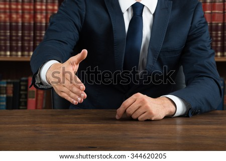 Midsection of lawyer offering handshake while sitting at desk in courtroom - stock photo
