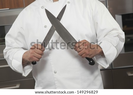 Midsection of male chef sharpening knives in commercial kitchen - stock photo
