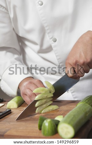 Midsection of male chef slicing cucumber on chopping board - stock photo