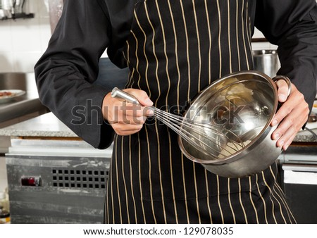 Midsection of male chef whisking egg in commercial kitchen - stock photo