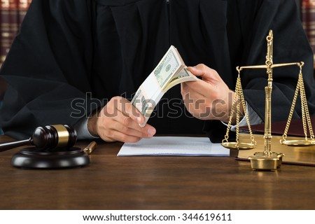 Midsection of male corrupt judge holding dollar bundle at desk in courtroom - stock photo