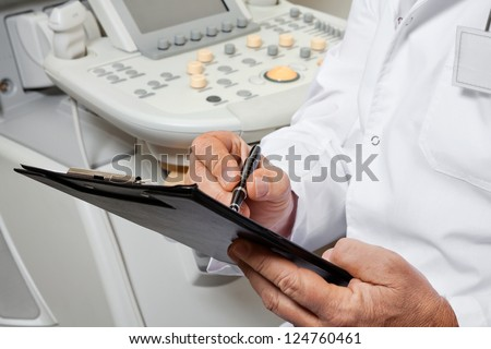 Midsection of male doctor writing on clipboard with ultrasonic machine in background - stock photo